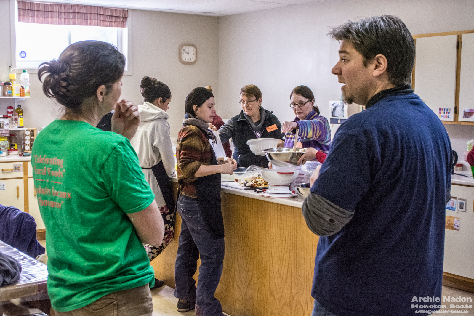 woman and man chatting while another group prepares food