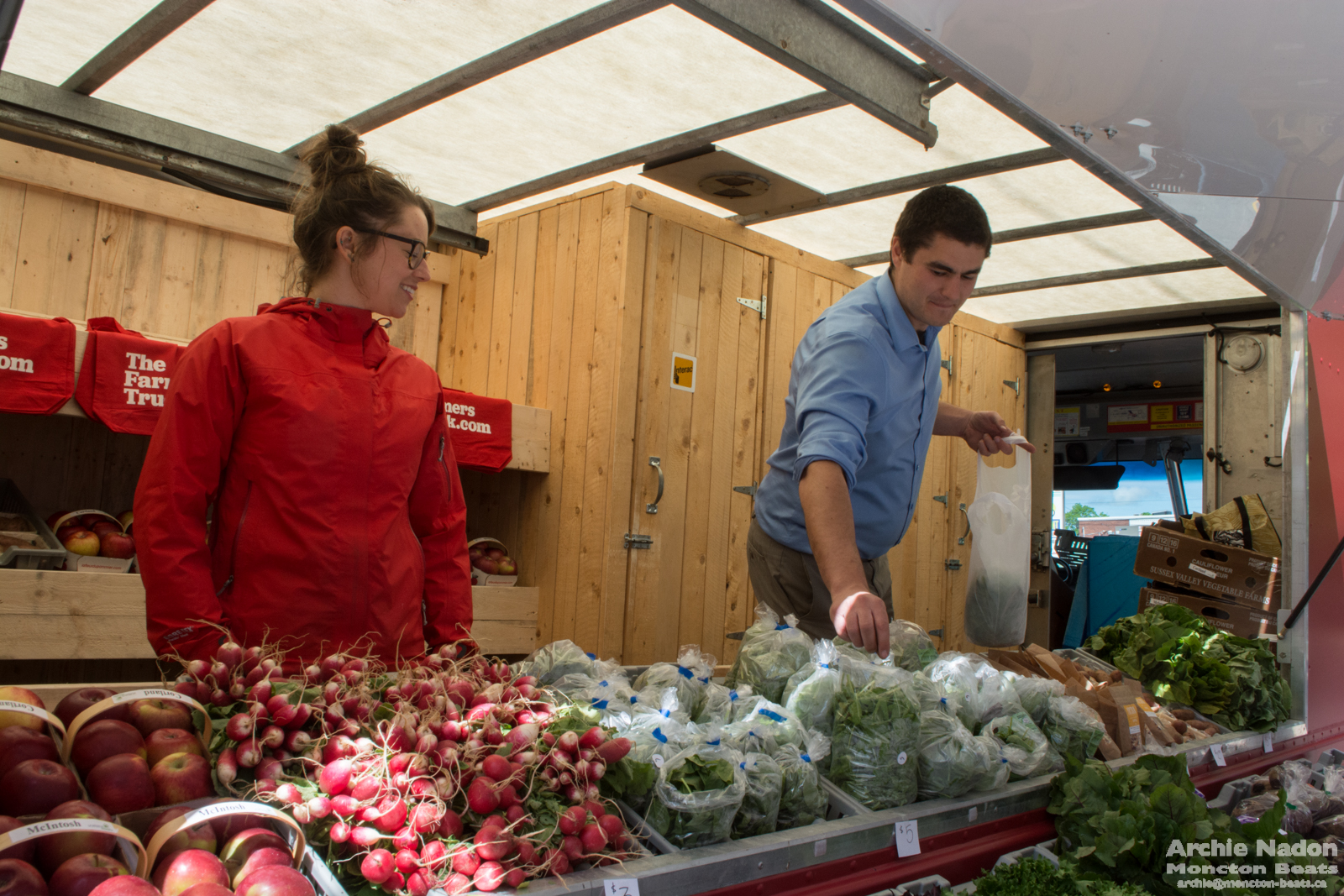 woman and man running mobile produce market