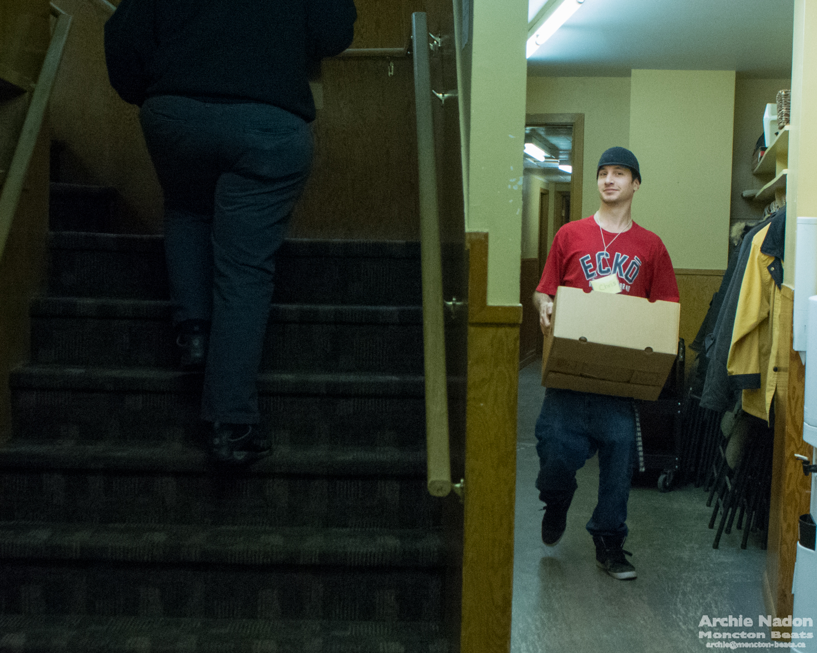 young man carrying box of groceries in a church basement