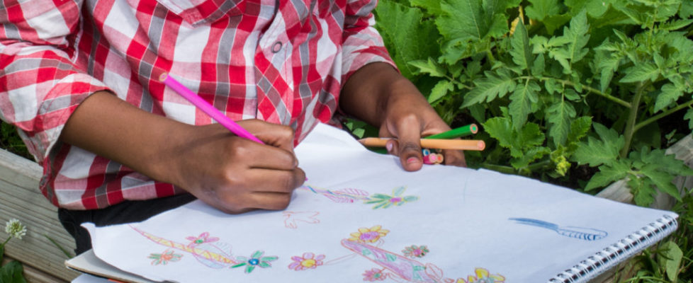 A girl drawing in the garden.