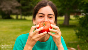 young woman eating a big tomato