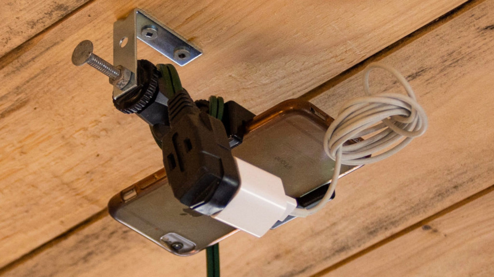 an iPhone mounted on ceiling with an L bracket an plugged in to a continuous power source.